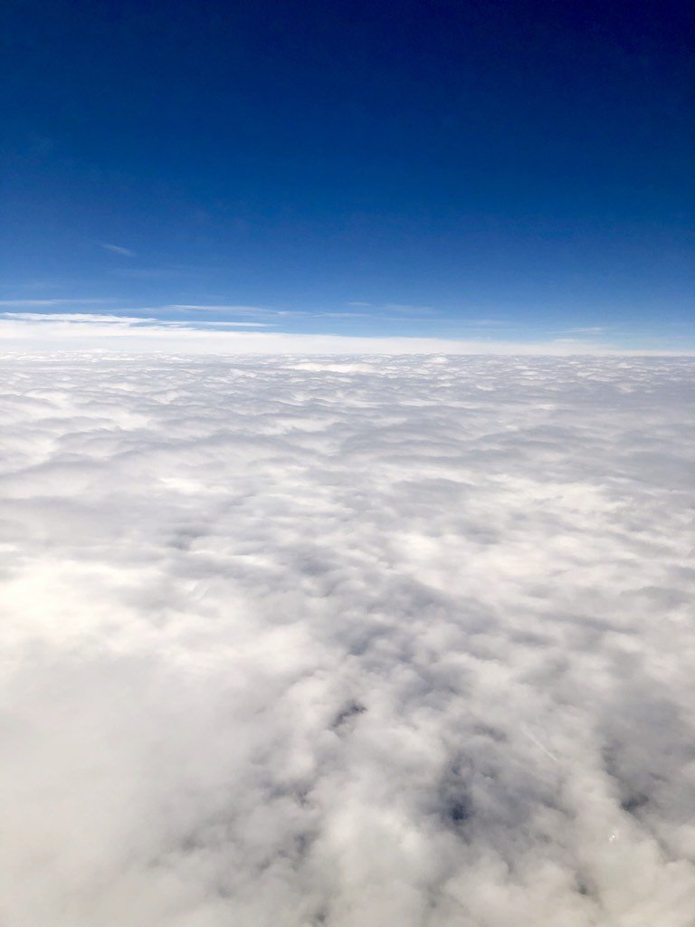 Clouds and blue sky from a plane window
