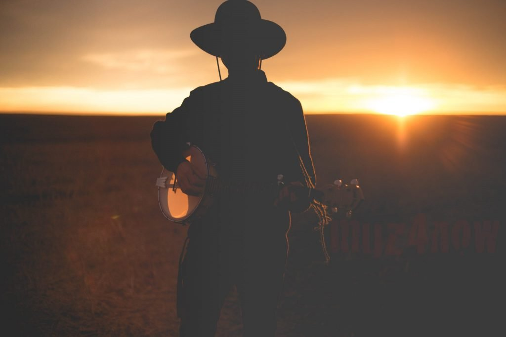 Someone with a wide-brimmed hat holding a banjo in the sunset - photo by Priscilla Du Preez