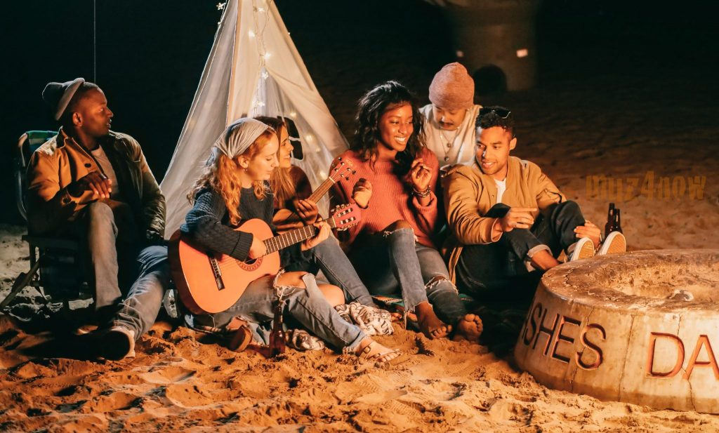 friends playing instruments at a beach campfire