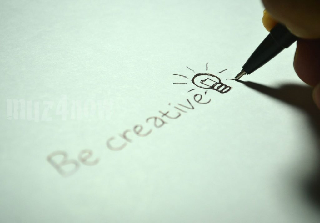 """A hand with a pen writing """"Be creative"""""""