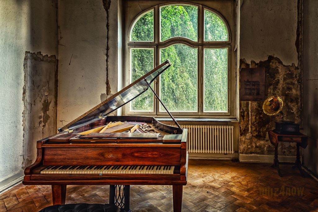 A grand piano with the lid up in a dilapidated room with a large window