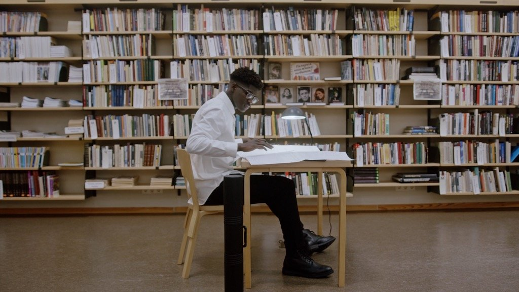 A young person sitting at a table in a library